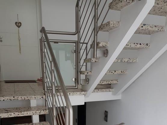 Treppengeländer aus Edelstahl mit Füllstäben und Milchglas an den Podesten
