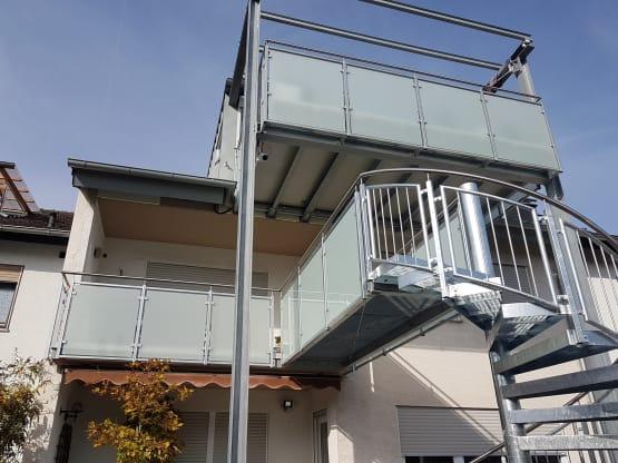 Stahlbalkon feuerverzinkt mit Faserzementbelag und feuerverzinktem Geländer mit Glasfüllung