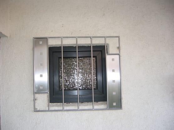 Fenstergitter gefertigt aus geschliffenem Edelstahl mit Zierblechen
